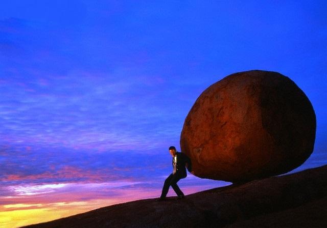 Businessman Pushing Large Rock up Hill